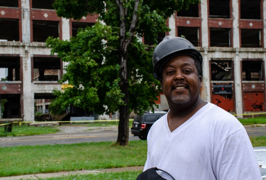 Christopher Burns is shown wearing a hard hat and white t-shirt standing across from the Packard Plant cleanup site.