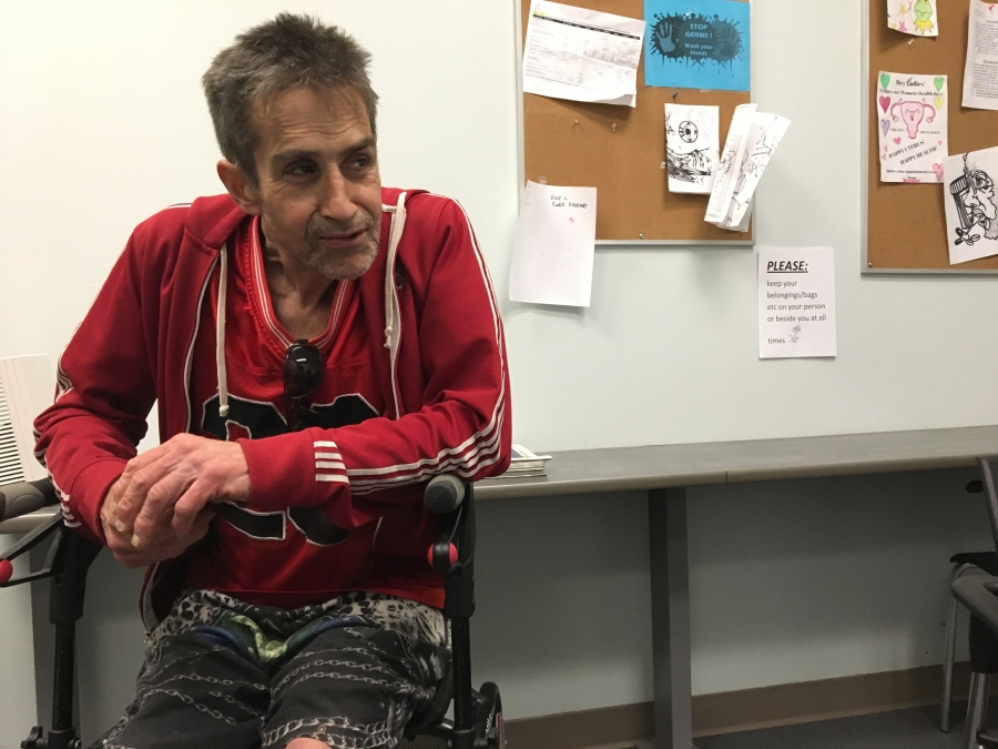 A man with a red sweatshirt sits in a clinic