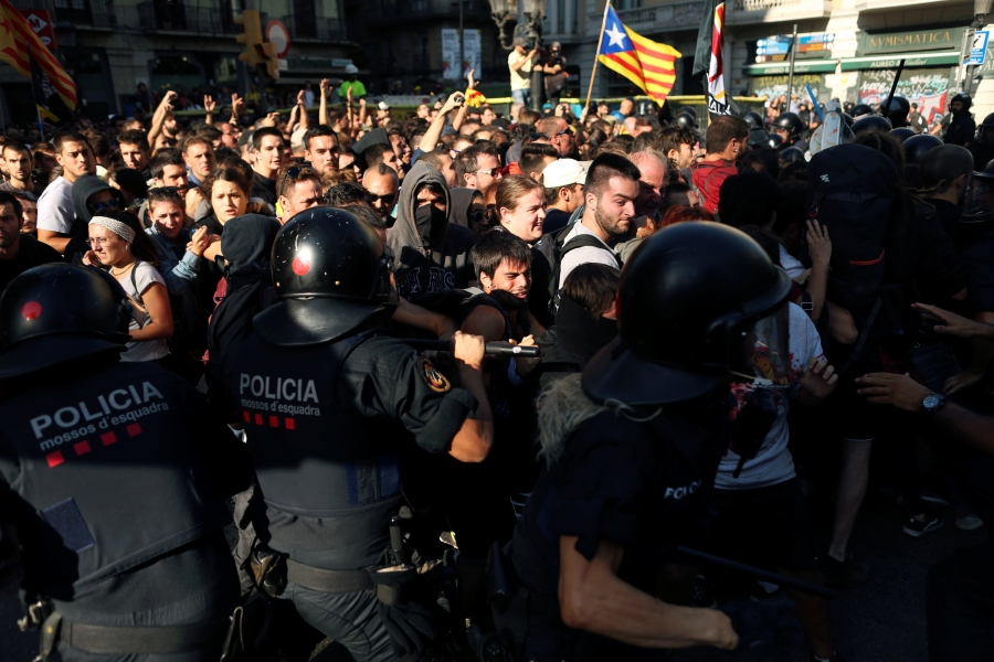 protesters clash with a Catalan flag waving in the background