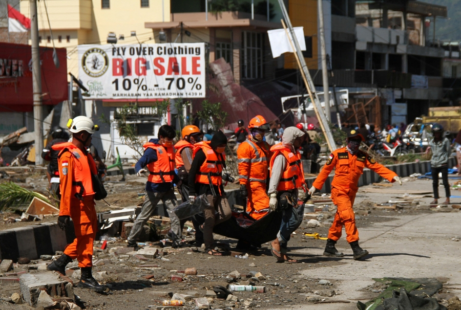 rescue workers dressed in orange carry a person on a gurney