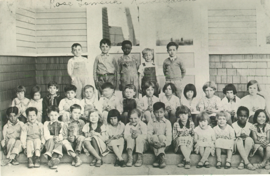 black and white photo of classroom, three rows of young children in shorts