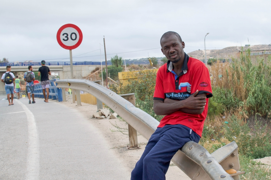 A migrant from Guinea sits on a railing outside outside of a detention center in Melillla, Spain