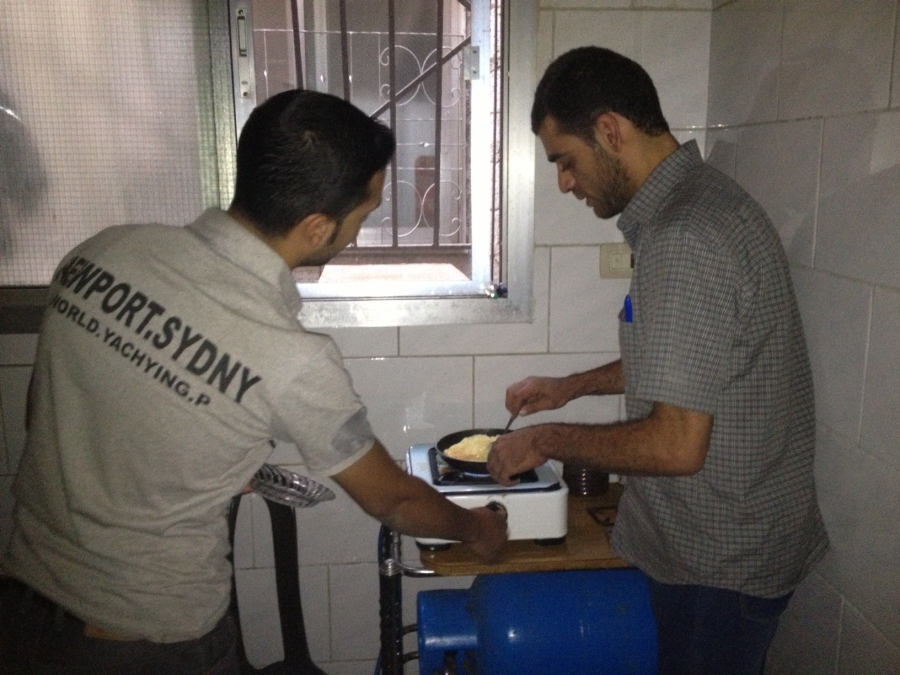 two men standing in a small, dark kitchen making eggs on a hotplate