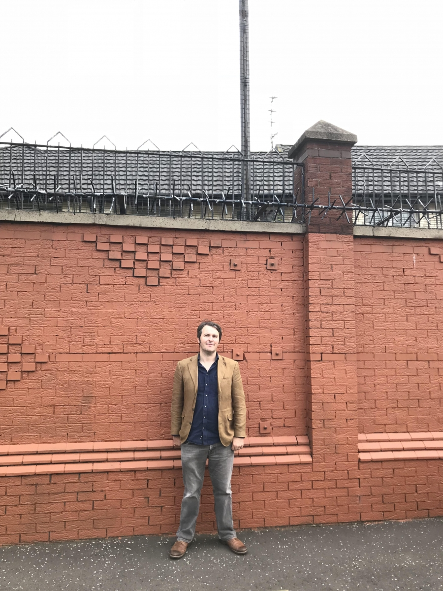 The writer Garrett Carr, standing by one of Belfast's numerous 'peace walls'