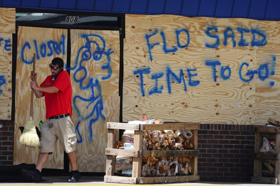 A man sweeps the entrance of a boarded up store before Hurricane Florence comes ashore in Carolina Beach, North Carolina, Wednesday
