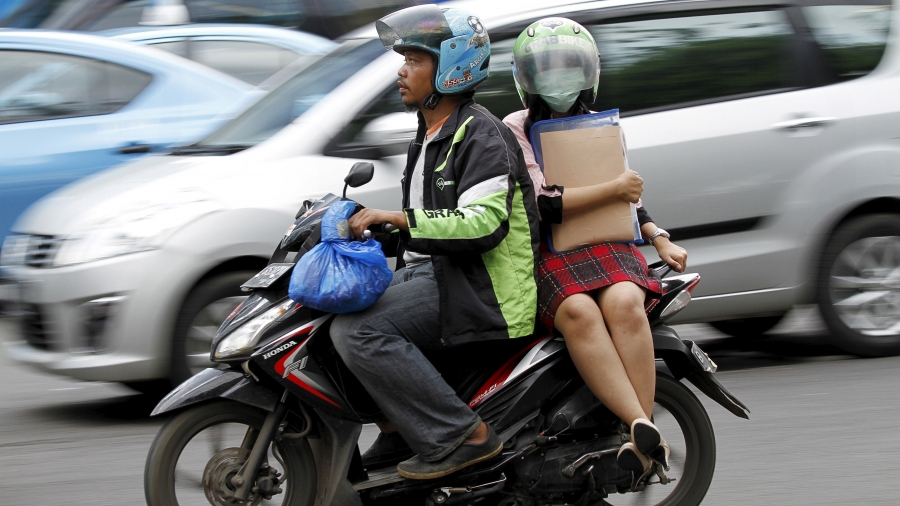 A woman rides on the back of a motorbike, part of the GrabBike ride-hailing service, on a busy street in central Jakarta, Indonesia