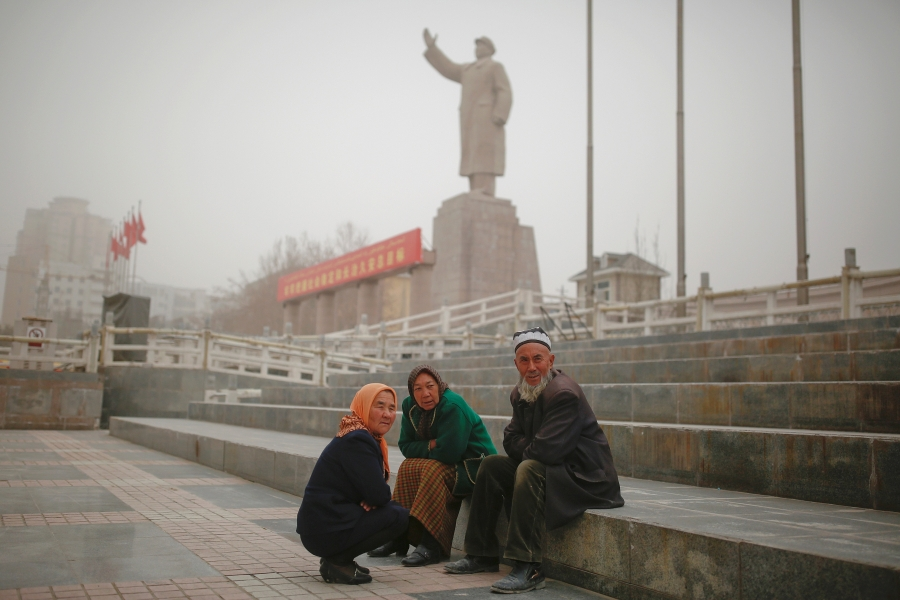 Ethnic Uighurs sit near a statue of China's late Chairman Mao Zedong in Kashgar.