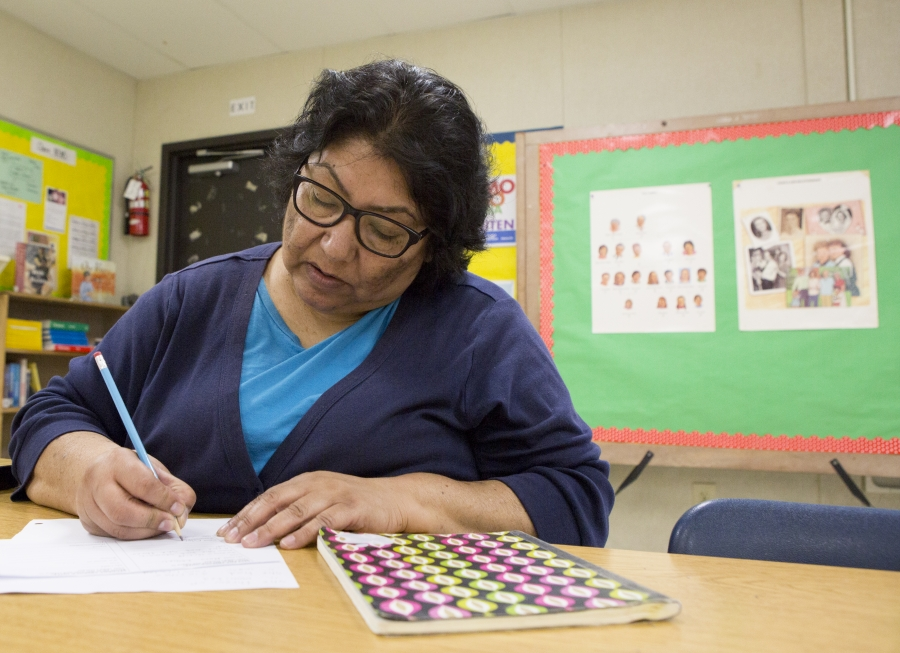 Woman sits at desk in elementary classroom, writing on sheet of paper with a pen