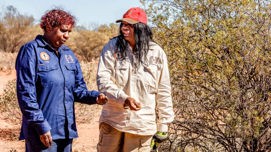 Two women speak to each other as they walk through the bush in an arid desert.
