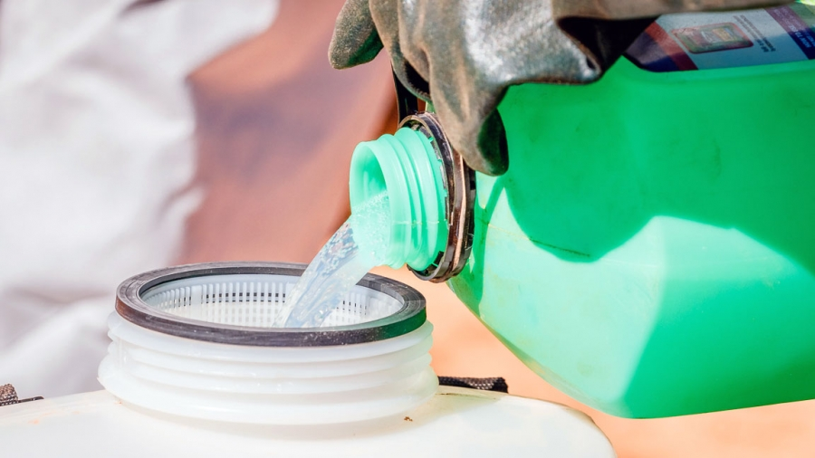 A gloved hand holds a green bottle and pours a clear liquid into another plastic container.