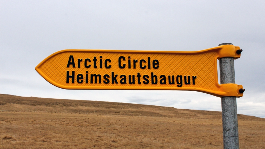 "A yellow metal sign with the words ""Arctic Circle"" written in black points the way to the Arctic Circle on a tiny Icelandic island."