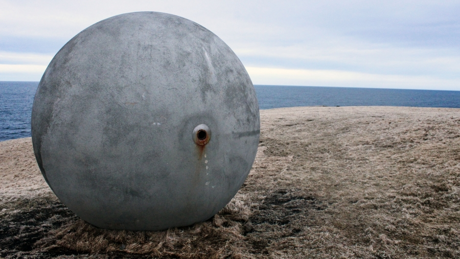 A large grey sphere sits on a grassy hill by a sea
