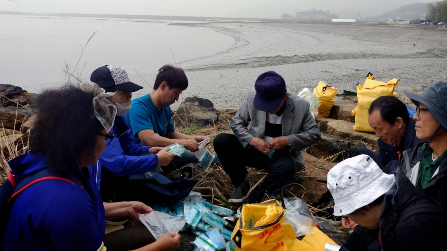 A group of people sit in a circle. Between them are blue bags and plastic bottles, which they are filling with rice, USB drives and tiny Bibles.