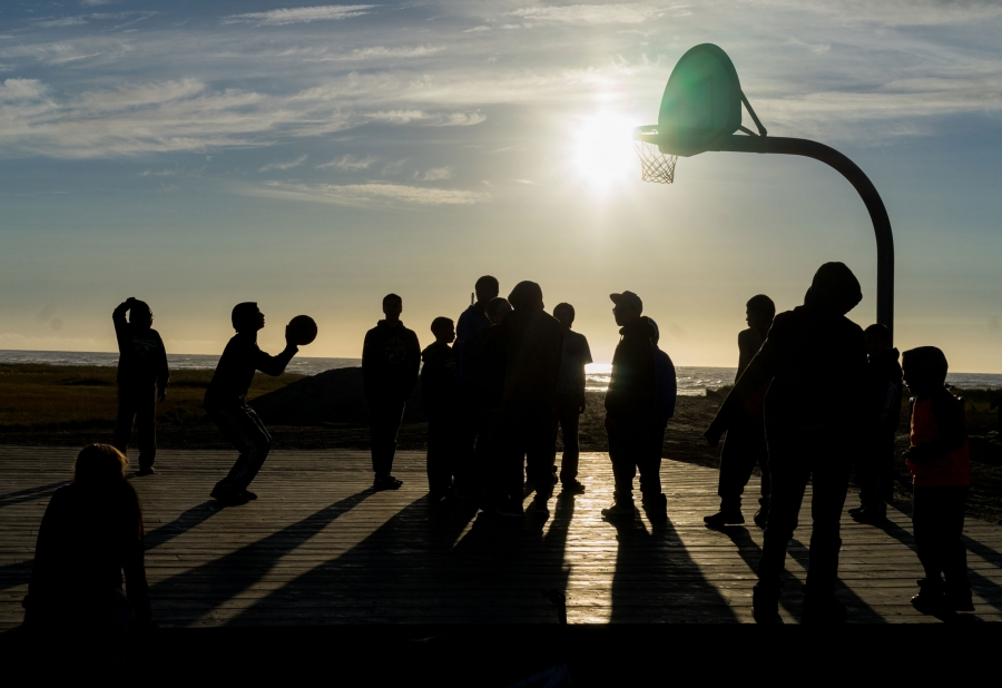 Children are silhouetted against the setting sun as they play basketball.