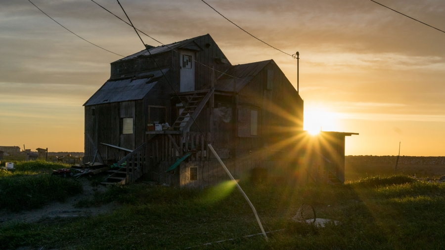 The sun sets behind a wooden home