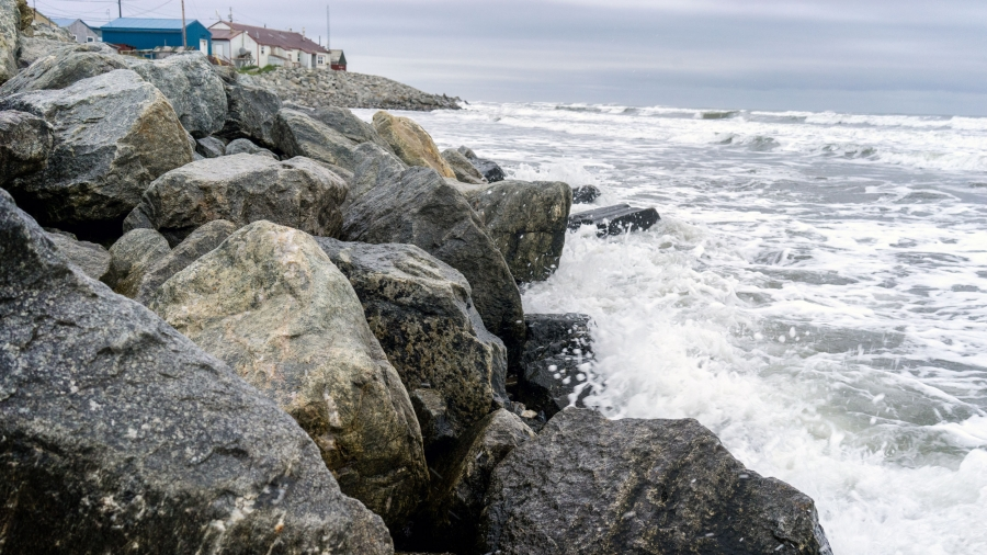 Waves crash into rocks. A house stands in the background.