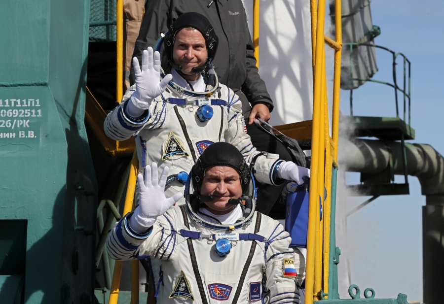 International Space Station crew members are shown in their space suits standing on a yellow ladder.