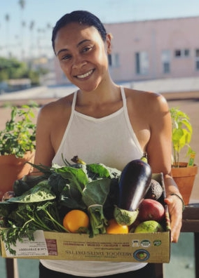 A young woman holds a box of veggies.