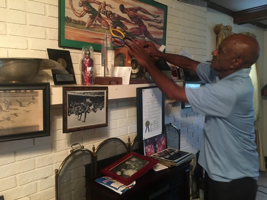 Leo Coleman places photos, paintings and medals over his fireplace