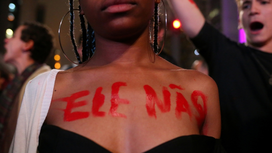 "A woman writes ""Not Him"" in red letters on her bare chest."