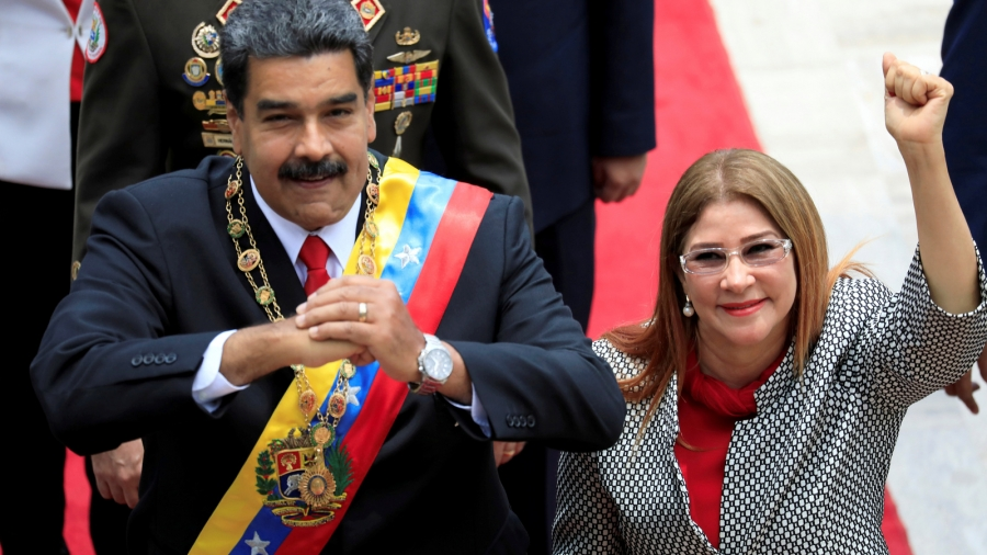 Venezuela's President Nicolás Maduro and his wife Cilia Flores gesture during arrival for special session