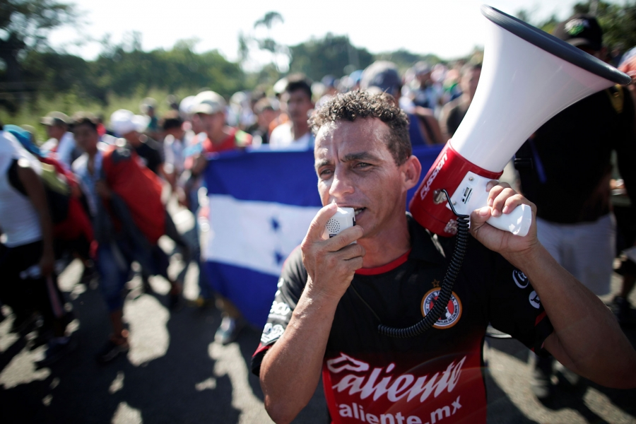 Central American migrants shout slogans and one man spoke into a megaphone.