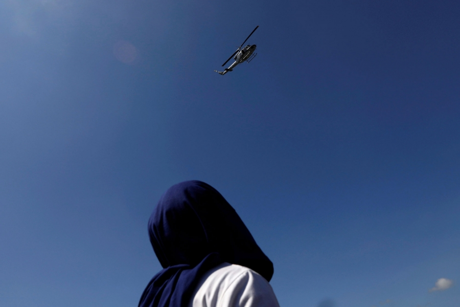 A Central American migrant is shown looking up as a military helicopter flies overhead.
