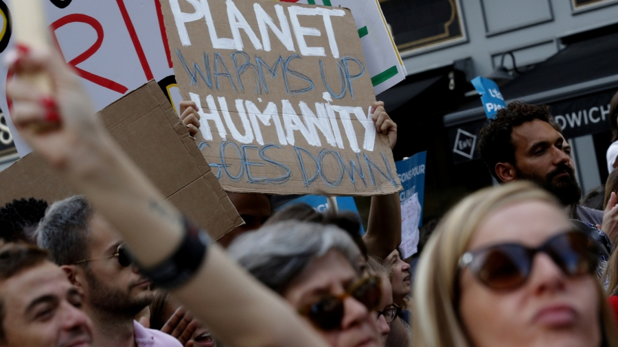 "Protesters hold up a sign ""Planet Goes Up, Humanity Goes Down."""
