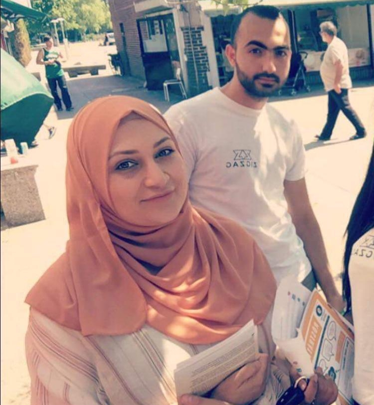 Alana Abdalla wears an orange headscarf and carries election materials