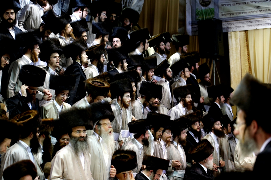 a large group of ultra-orthodox men dressed in traditional garb