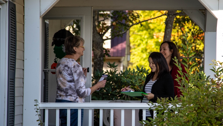 Safiya Wazir is shown with a green clipboard in hand standing on the front porch, speaking with a resident of Concord, New Hampshire.