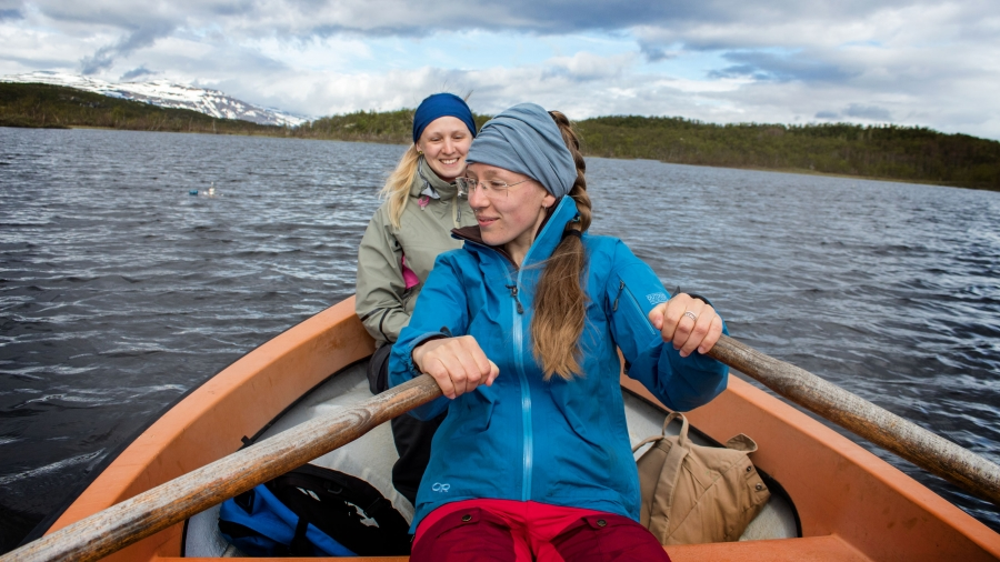 Two female student researchers in a row boat on a lake.