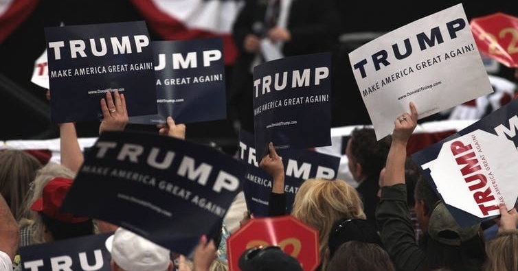 Supporters of President Donald Trump wave campaign signs.