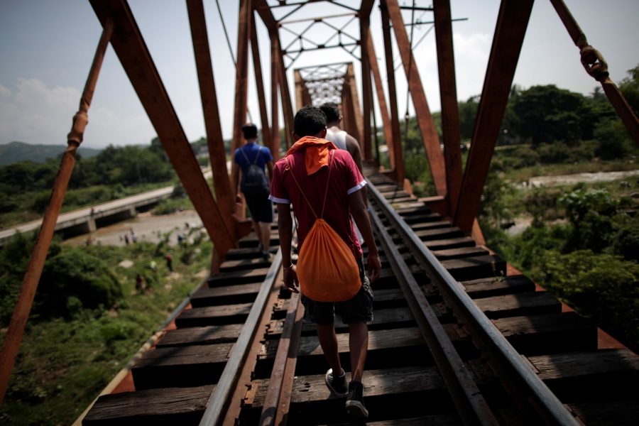Migrants are shown walking along train tracks with their backs to the camera in Arriaga, Mexico Oct. 26, 2018.