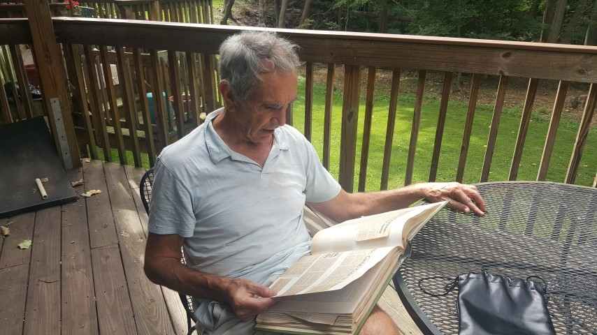 Andrew Larkin looks through his scrapbook on his back porch