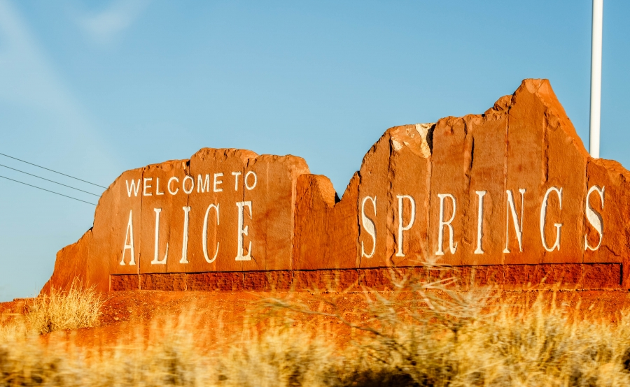 A stone sign for Alice Springs is shown in the shape of the mountain skyline.