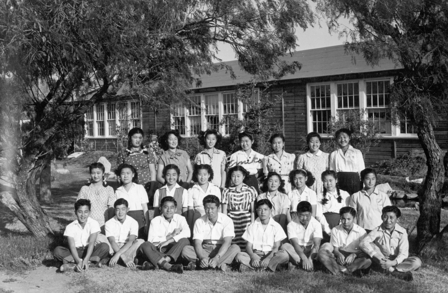 Three rows of students pose in front of a building