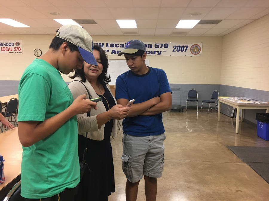 Woman stands with two young men leaning over her, looking at phone