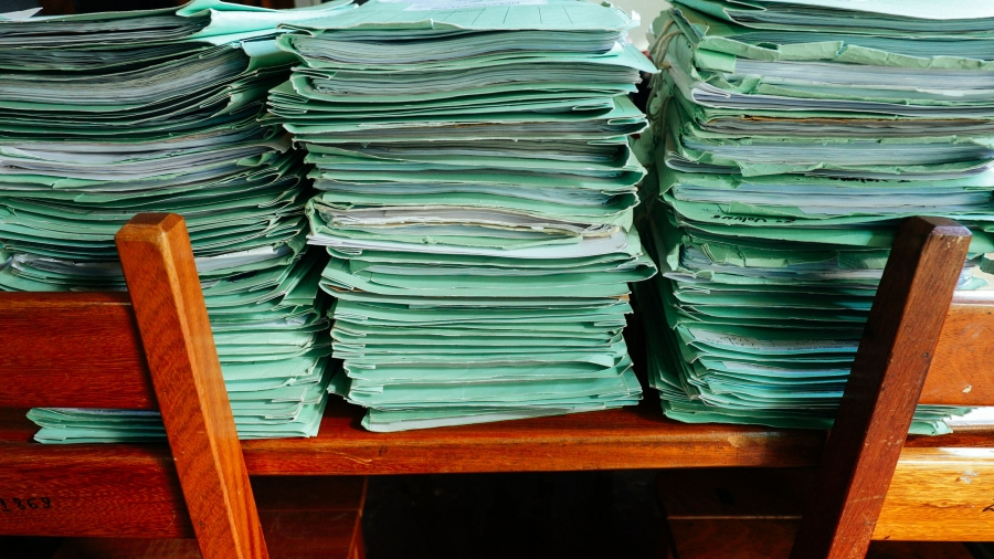 Piles of boxes contain folders of mostly unpaid fines for deforestation violations, Selva says.
