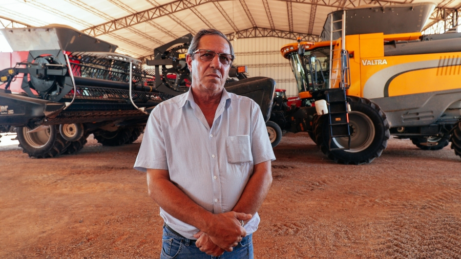 A man poses in front of heavy farm machinery.