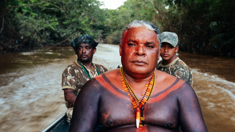 An Indigenous Man wearing beads, his chest decorated with red and black paint, sits in a speedboat. There are two men in camouflage behind behind him.