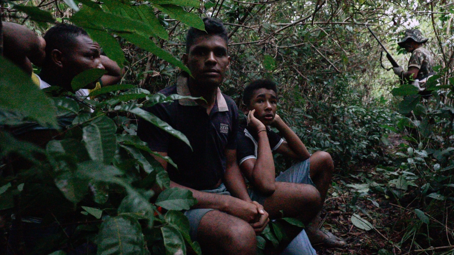 Three boys are on their knees in the jungle, with their hands clasped behind their heads.
