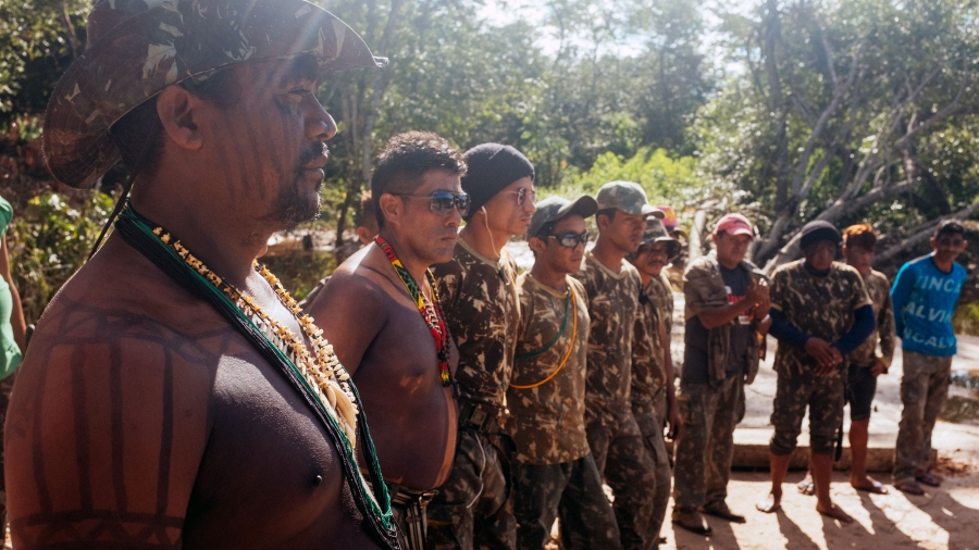 Men wearing camouflage stand in a line.