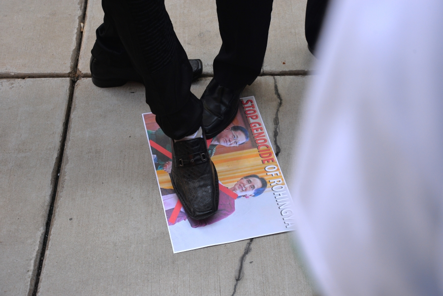 A picture of Myanmar politician Aung San Suu Kyi is on the ground and a foot is stepping on the photo.