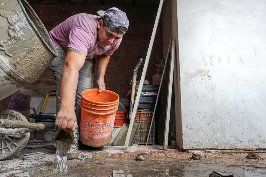 a man works with bricks and cement to build a house in argentina
