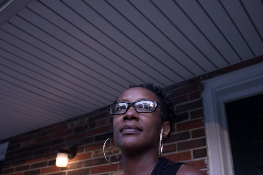 a woman stands in front of her home in st louis