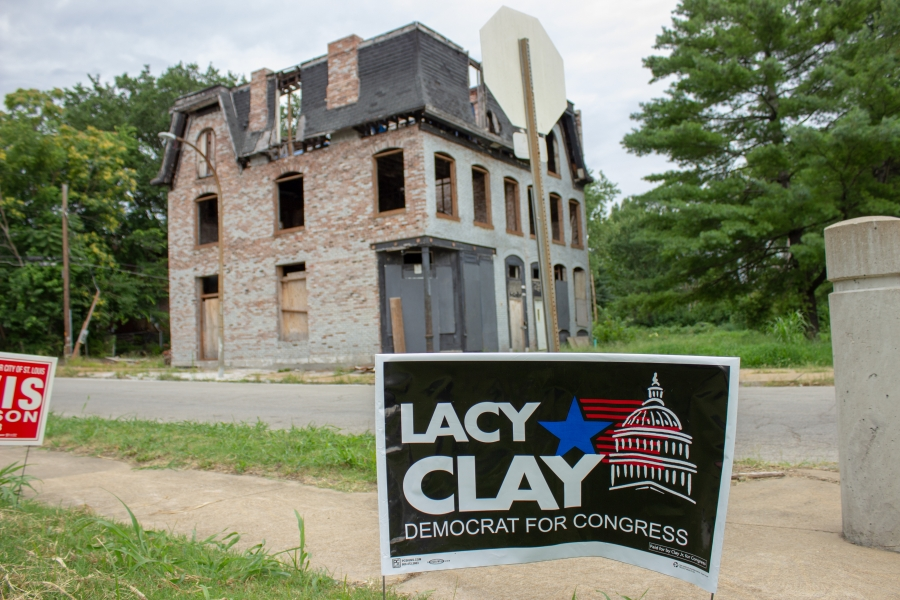 a lacy clay yard sign in front of an abandoned house in st louis