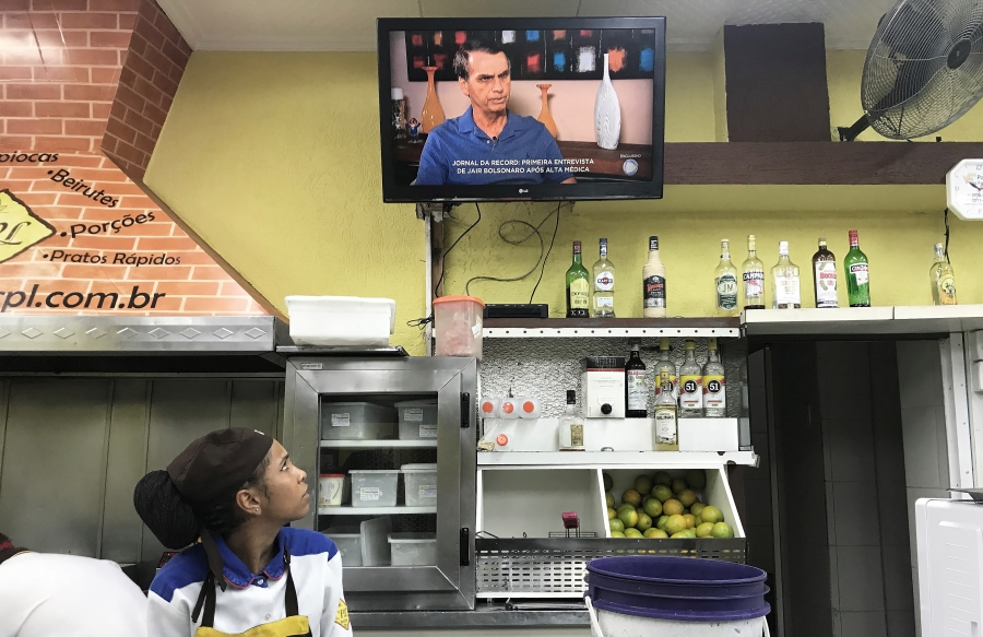 a woman working in a kitchen watches the tv over her shoulder