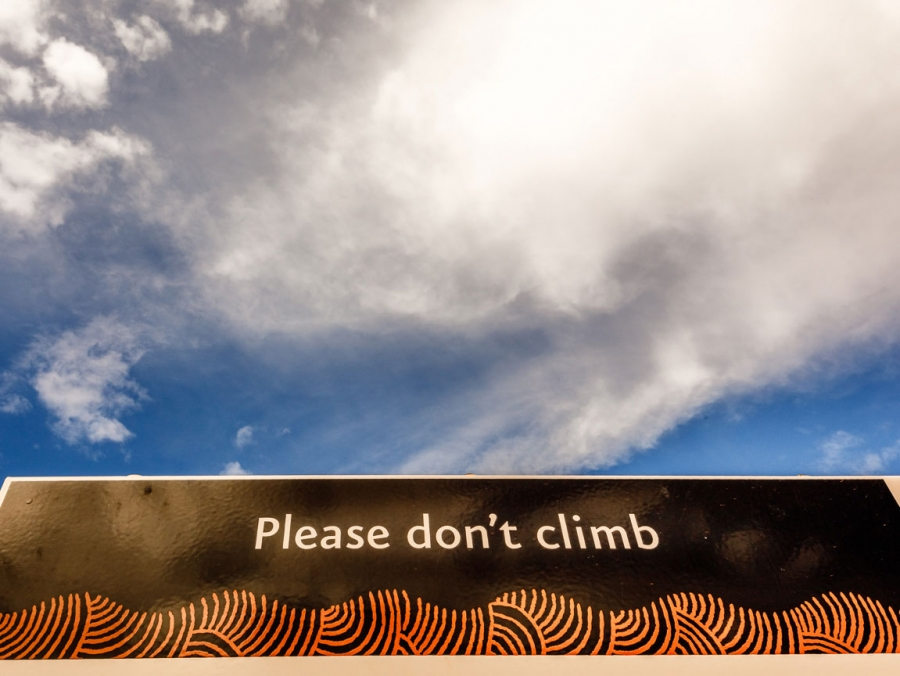 Signage at the base of Uluru reads, 'please don't climb.'