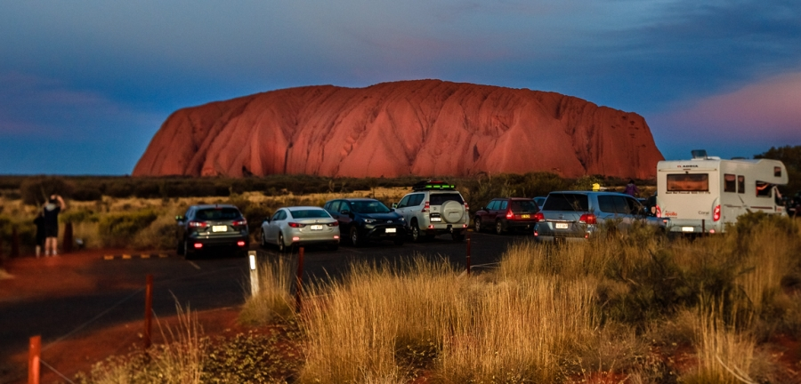 Cars are shown in the foreground near the base of Uluru, cast in red light from the sunset.